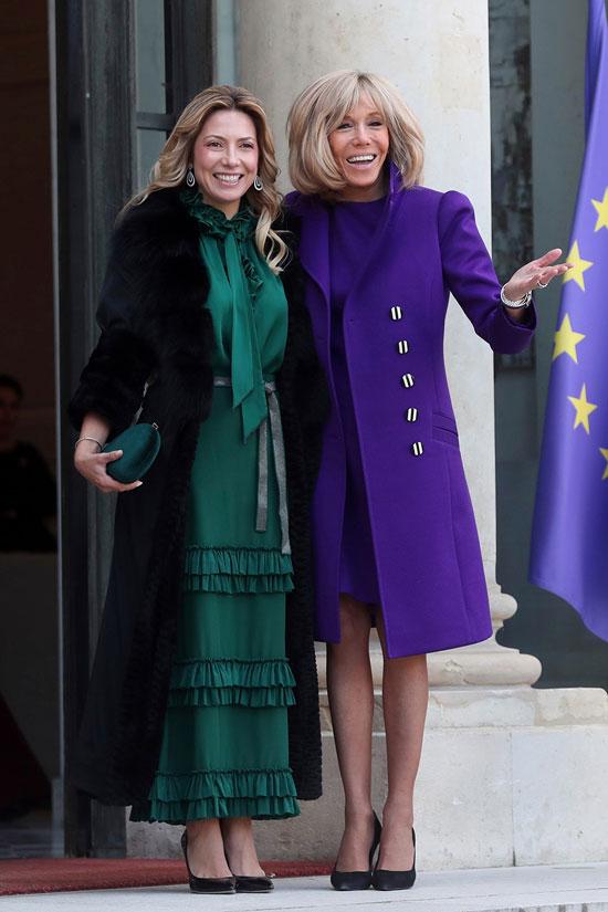 Брижит Макрон в фиолетовом пальто, платье и черных лодочках