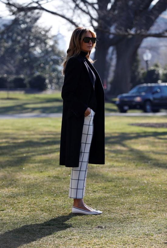 Мелания Трамп в белых брюках в клетку и черном пальто