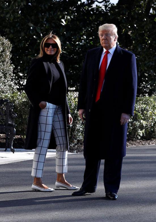Мелания Трамп в белых брюках в клетку, черном пальто и белых туфлях