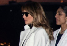 Мелания Трамп в джинсах скинни, белом пальто и рокерских ботинках с пряжками