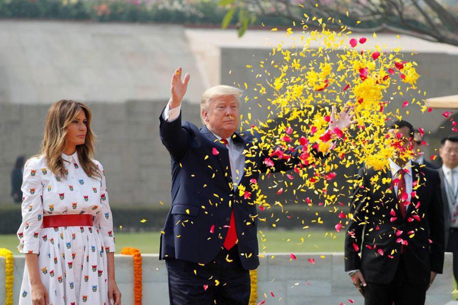 Мелания Трамп в белом платье с цветами, красном поясе и белых туфлях
