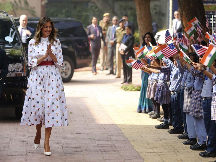 Мелания Трамп в белом платье с красным поясом и белых туфлях