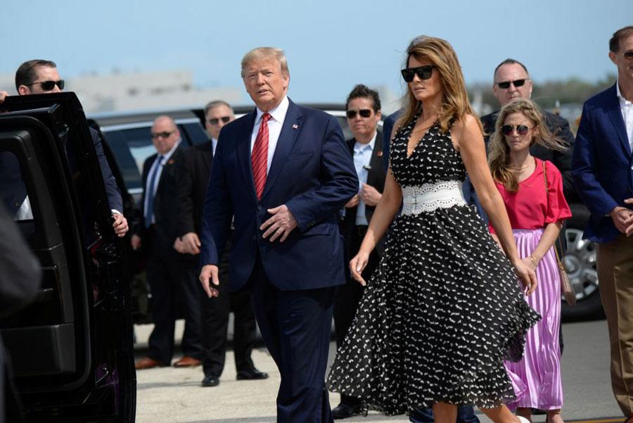 Мелания Трамп в черном платье с белым поясом и очках