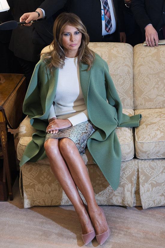 Мелания Трамп в белой блузе и зеленом пальто