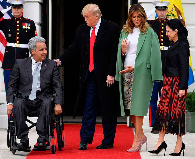 Мелания Трамп в белой блузе, зеленом пальто и грязно-розовых лодочках