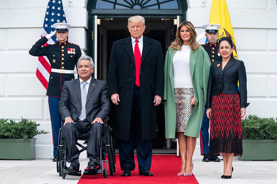 Мелания Трамп в юбке-карандаш, белой блузе и зеленом пальто