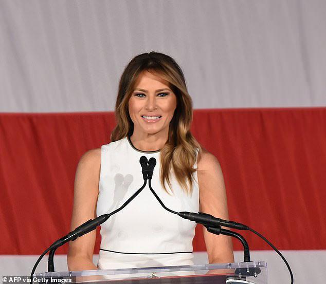 Мелания Трамп в белом платье миди без рукавов с черной отделкой вокруг шеи