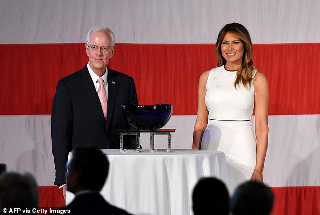 Мелания Трамп в белом платье с тонкой черной полоской вокруг шеи и на талии