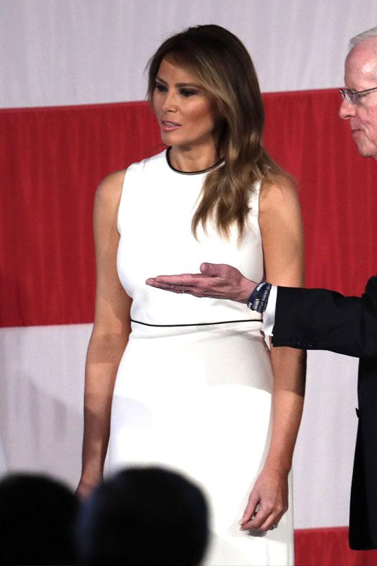 Мелания Трамп в белом платье без рукавов с с черной полоской на талии
