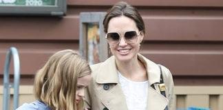 Анджелина Джоли в многослойном белом платье, мятом плаще и балетках весело улыбается