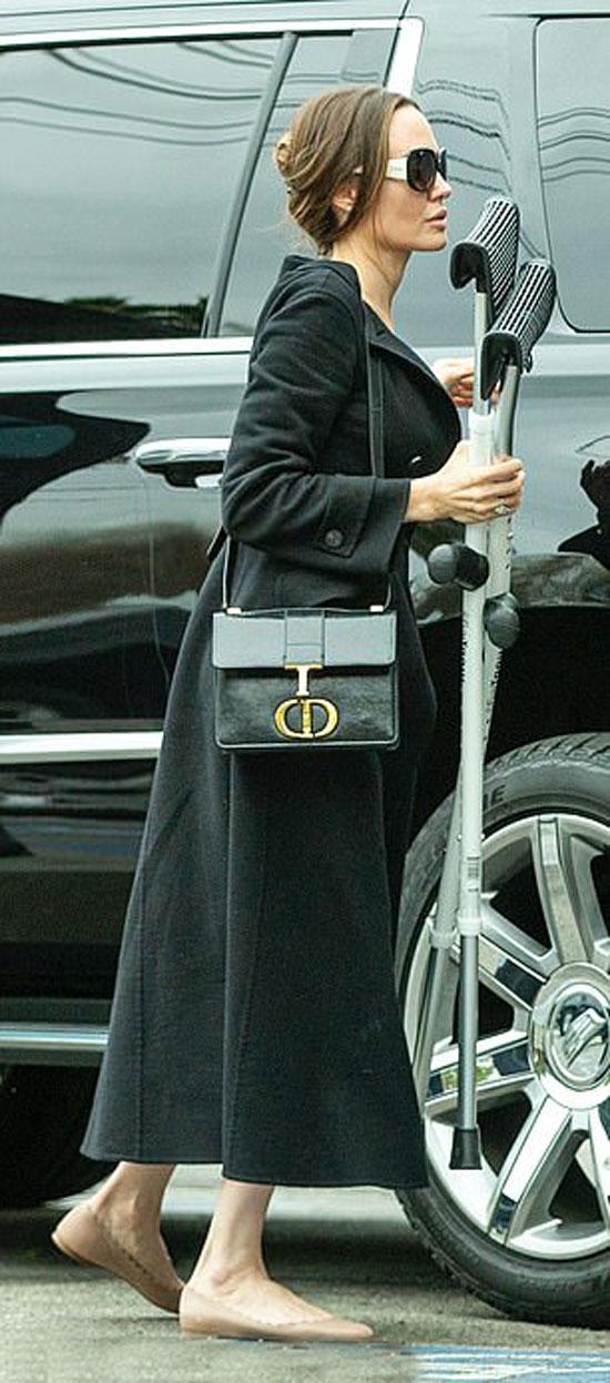 Анджелина Джоли в платье, черном пальто и балетках
