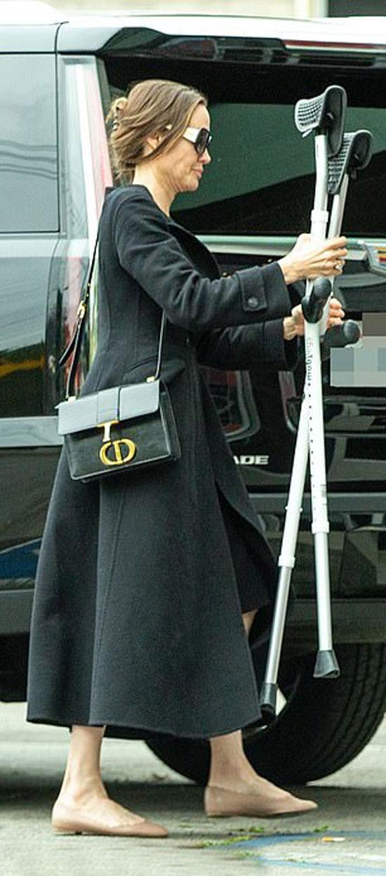 Анджелина Джоли в черном платье-миди, пальто и с дорогой сумкой
