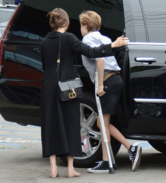 Анджелина Джоли в черном длинном пальто, балетках и с сумкой