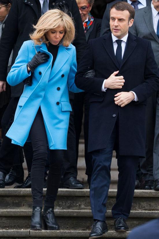 Брижит Макрон в голубом пальто, черной водолазке и джинсах