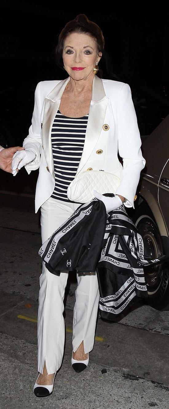 Джоан Коллинз в брючном костюме, туфлях, с белым клатчем и черным шарфом
