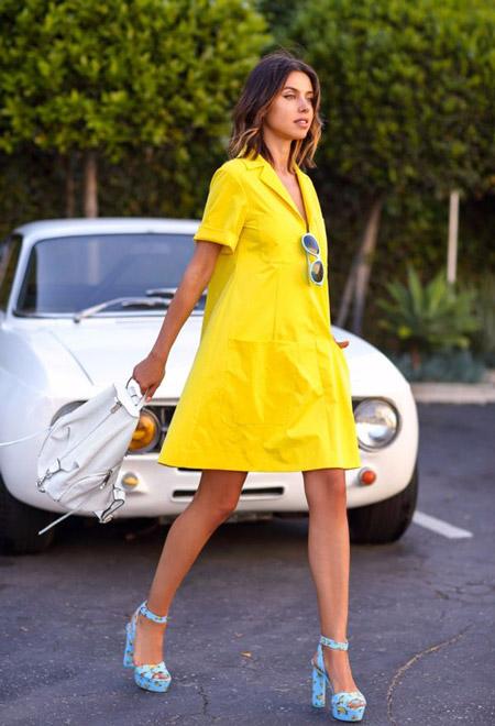 Девушка в желтом летнем платье и голубых босоножках