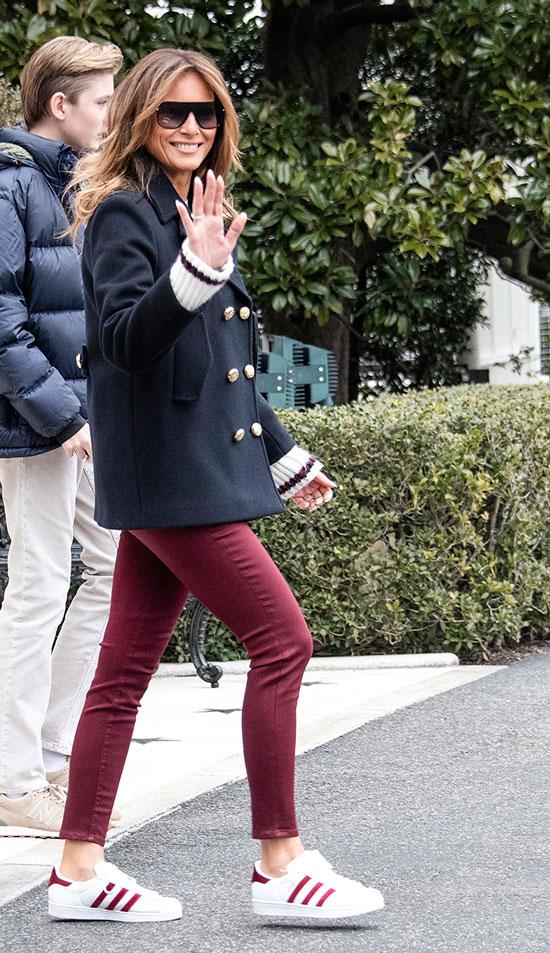 Мелания Трамп в бордовых джинсах, темно-синем пальто и белых кроссовках