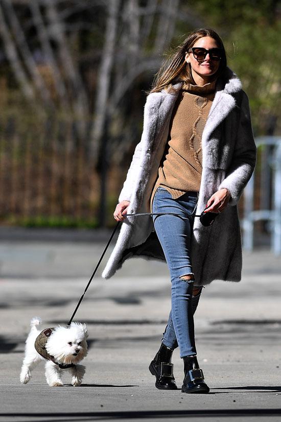 Оливия палермо в свитере, черных ботинках, синих джинсах и шубе