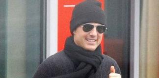 Том Круз в сером свитере, классических джинсах, шапке и шарфе улыбается прохожим