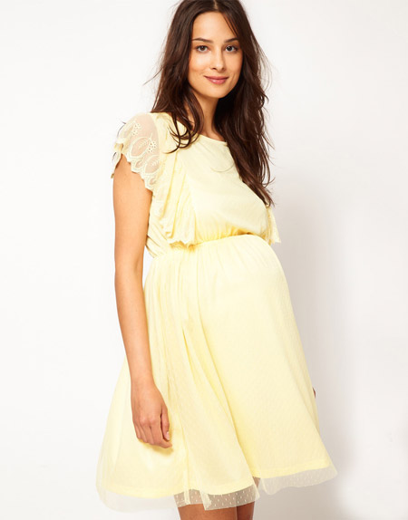 Девушка в светло-желтом, коротком платье для беременных