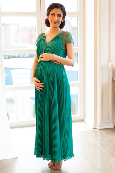 Девушка в длинном платье для беременных плиссе зеленого цвета