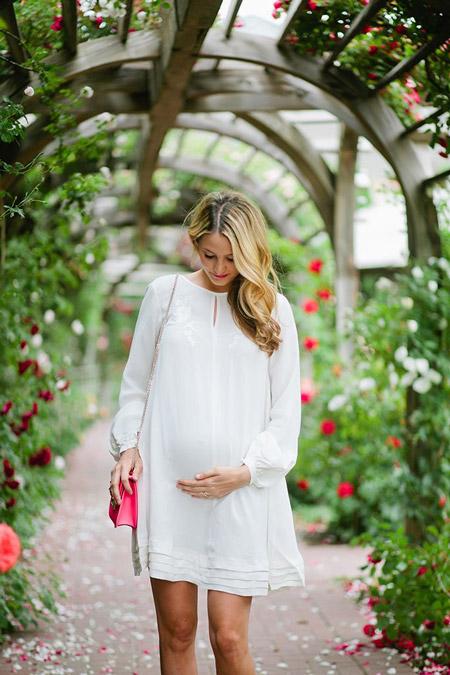 Девушка в свободном, белом платье для беременных