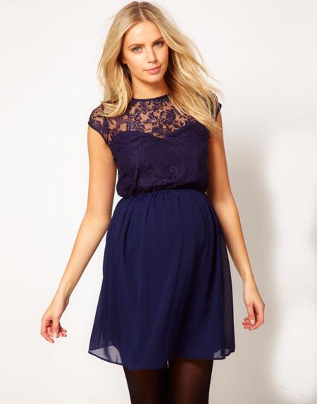Девушка в красивом, синем платье для беременных с ажурным верхом