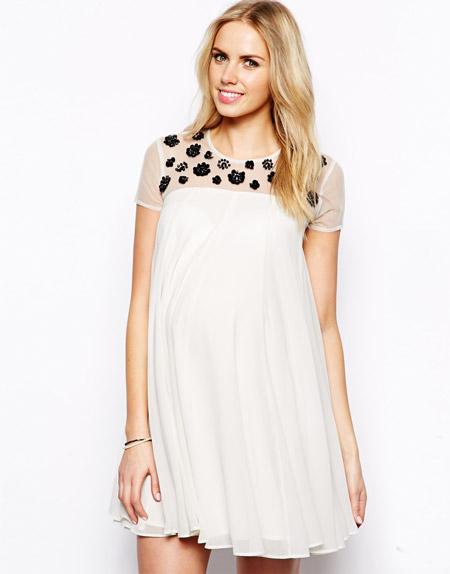 Беременная девушка в белом платье с прозрачным верхом