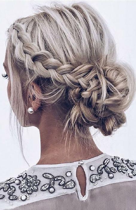Девушка со свободным пучком из голландской косы на светлых волосах