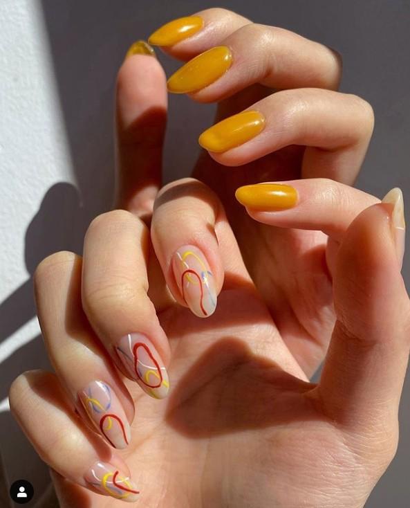Оранжевый маникюр с абстрактными узорами на овальных ногтях