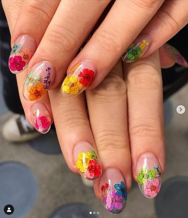Разноцветный цветочный маникюр на прозрачных овальных ногтях