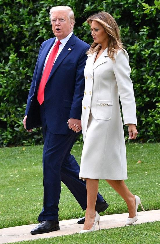 Мелания Трамп в белом пальто двубортном пальто с накладными карманами и лодочках