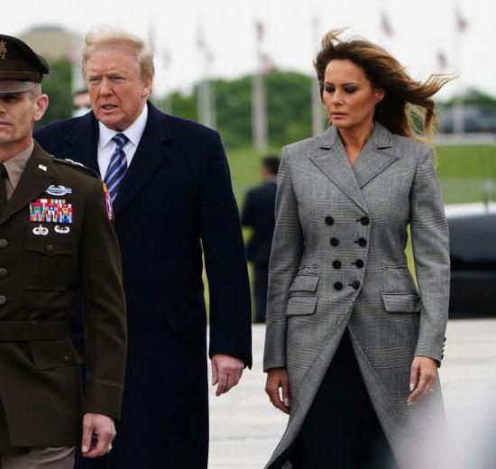 Мелания Трамп в сером двубортном пальто и черном платье-миди