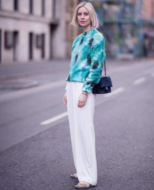 Девушка в белых брюках палаццо и толстовке с принтом