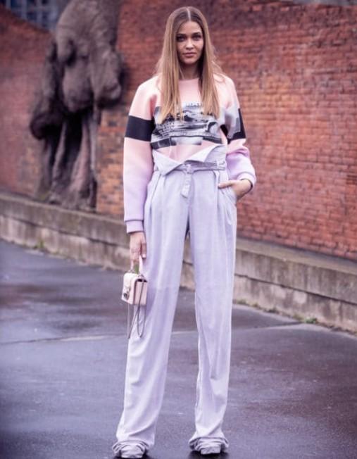 Девушка в серых брюках палаццо с высокой талией, розовая толстовка и мини сумочка