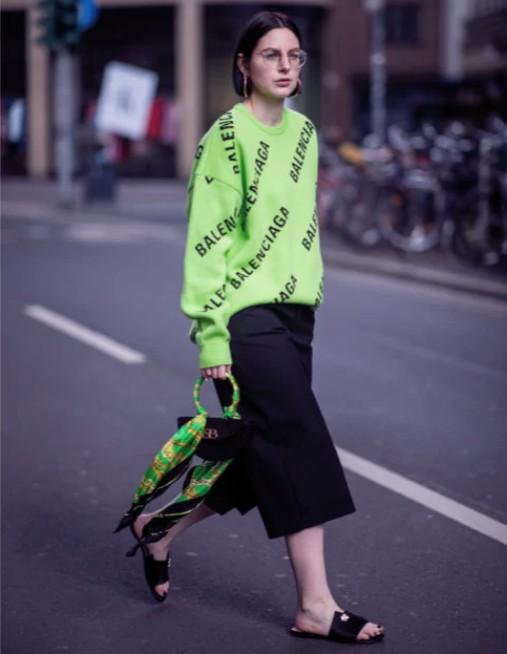 Девушка в зеленом свитере, черные укороченные брюки и простые шлепки