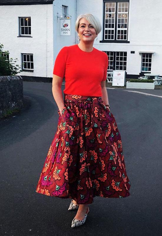 Женщина в красном топе и яркой юбке миди