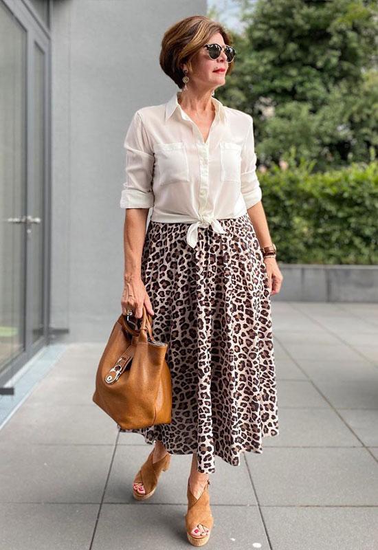 Женщина в белой блузе, юбке миди и босоножках