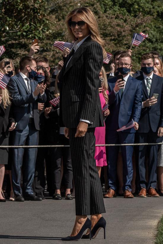 Мелания Трамп в брючном костюме и синих туфлях