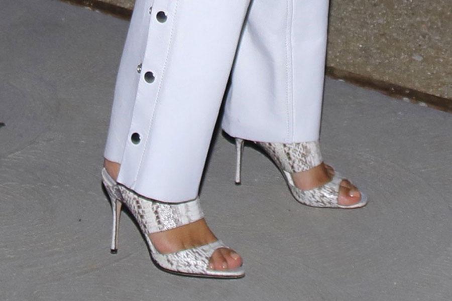 Ким Кардашьян в белых брюках и босоножках со змеиным принтом