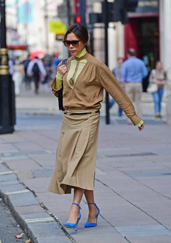 Виктория Бекхэм в юбке, синих туфлях и коричневой блузе