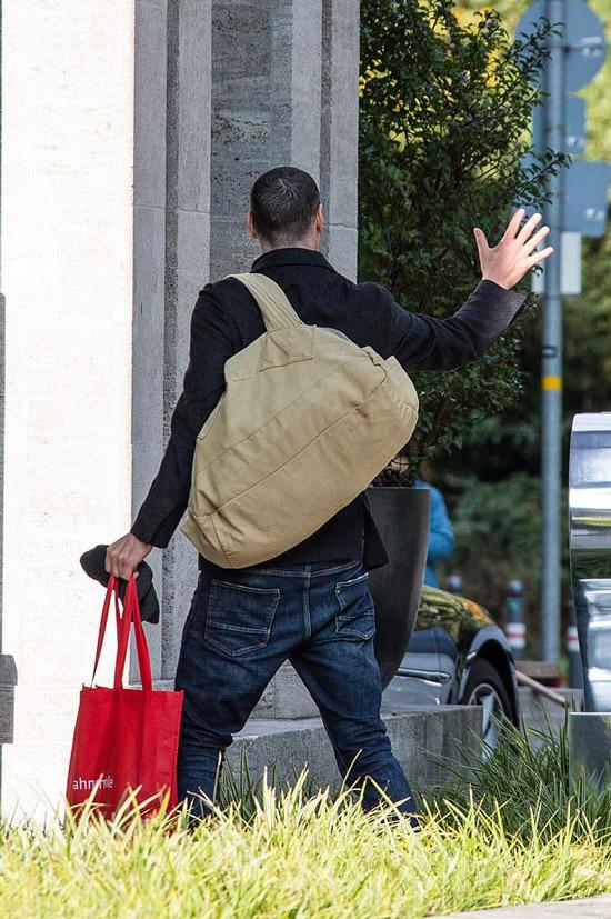 Киану Ривз в джинсах и ботинках машет рукой