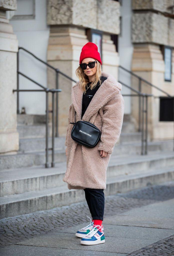Девушка в черных джинсах, теплое пальто тедди и кеды