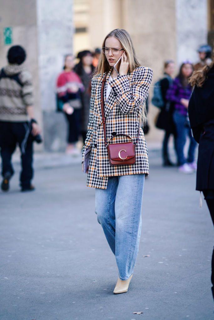Девушка в голубых широких джинсах, пиджак в клетку и боильоны