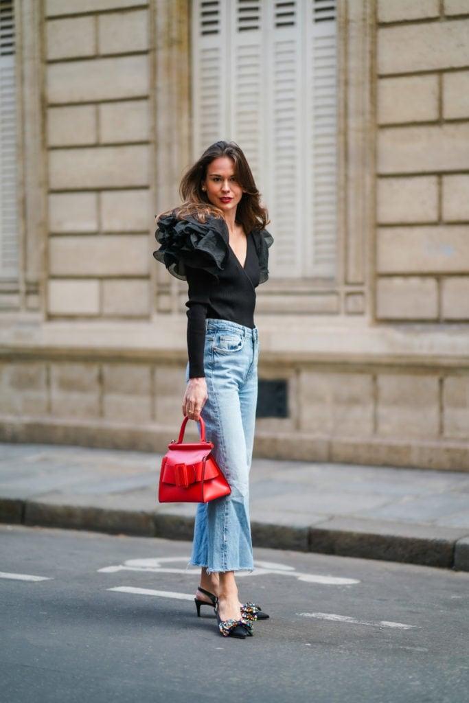 Девушка в голубых укороченных джинсах, черный топ с рюшами и туфли с украшениями