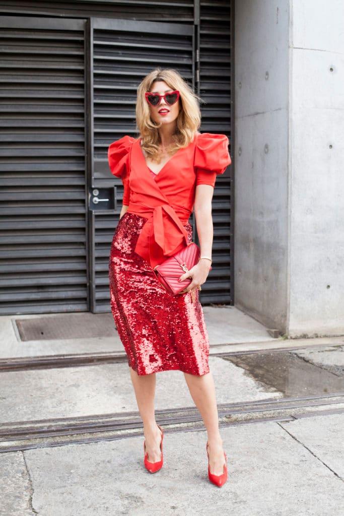 Девушка в красной юбке карандаш с пайетками, красной блузе с рукавами фонариками и туфлях лодочках