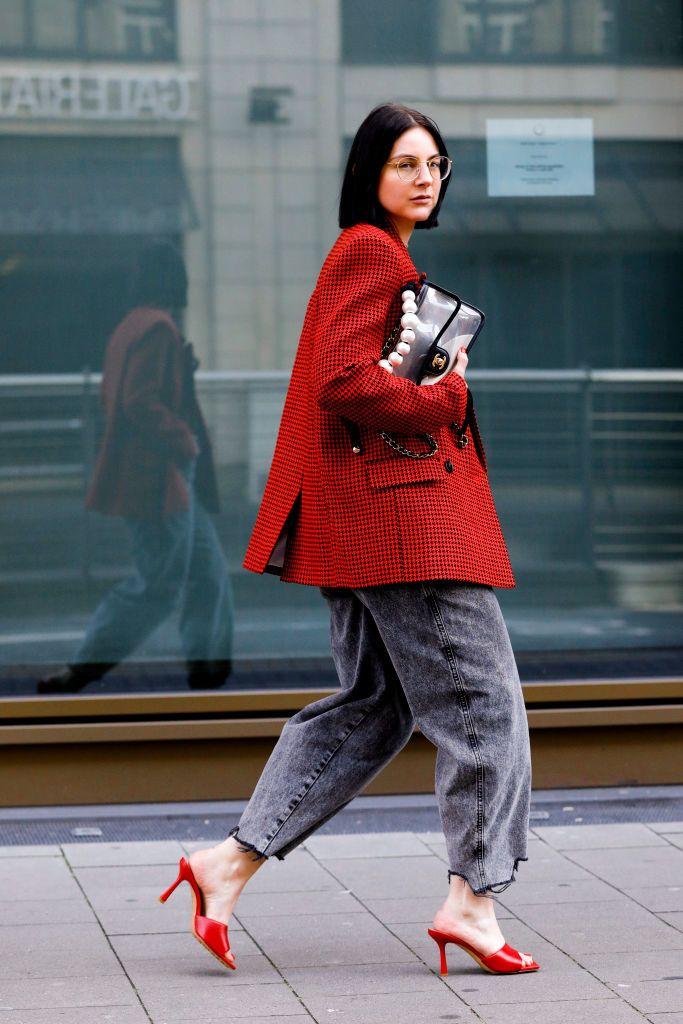 Девушка в серых широких джинсах, красный пиджак в клетку и красные мюли