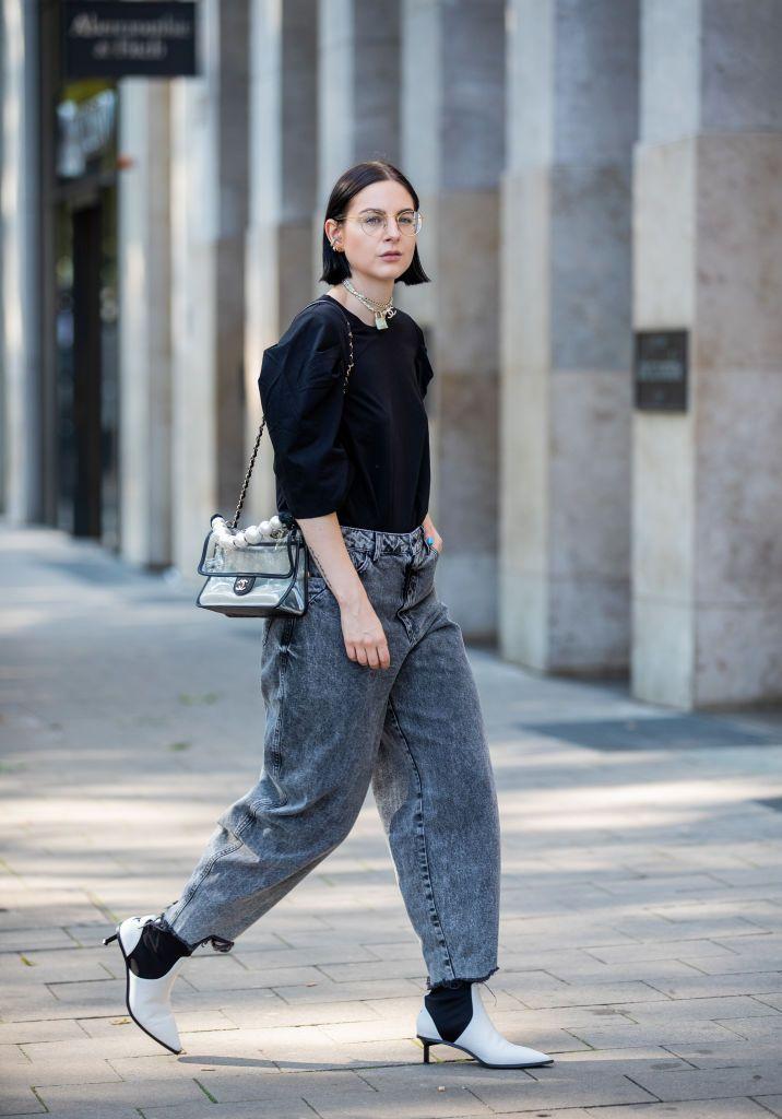 Девушка в широких серых джинсах, черная футболка и ботильоны