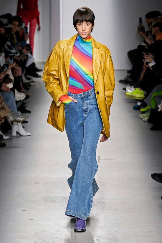 Девушка в синих джинсах клеш с разноцветной водолазкой, желтый кожанный плащ и ботильоны