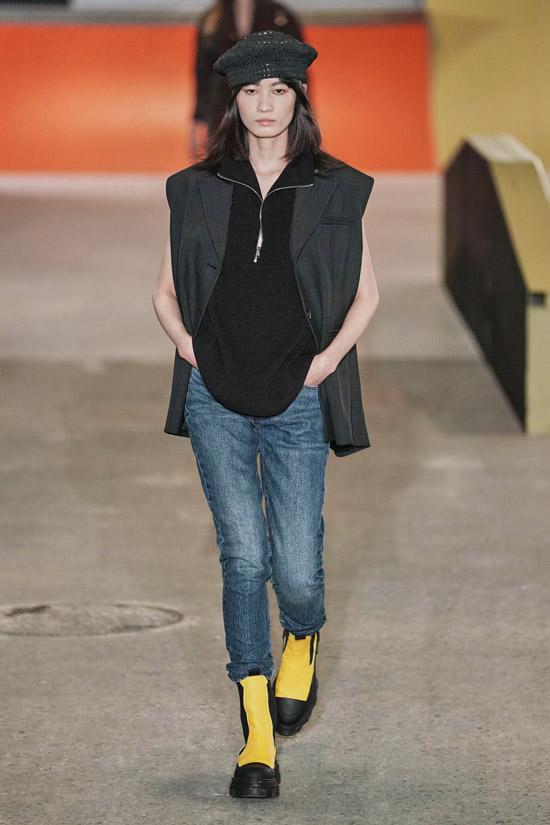 Девушка в синих укороченных джинсах, черная кофта и ботинки